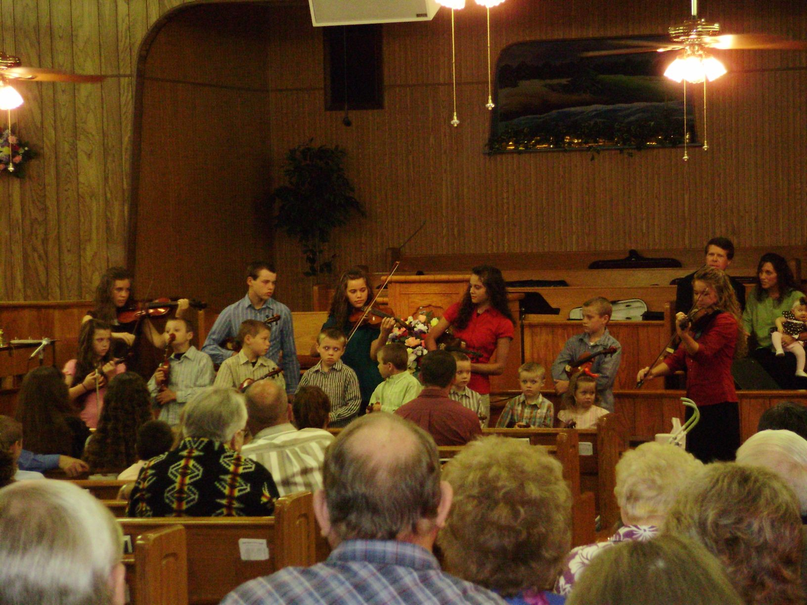 Duggar Children play their violins for the congregation